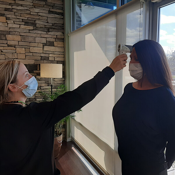 One of our team member checking the body temperature of the client upon arrival.
