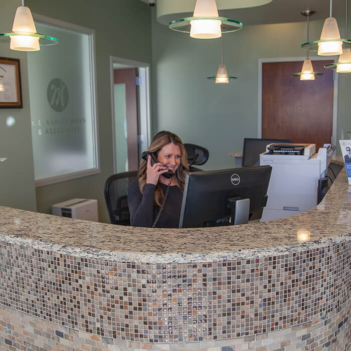 A team member answering phone calls at the reception area