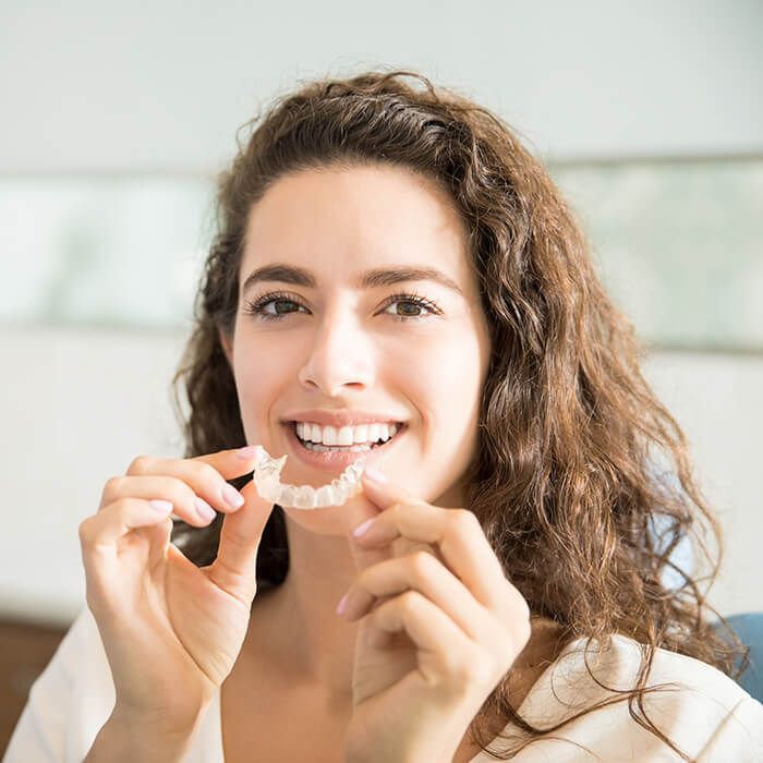 A female patient holding an Invisalign