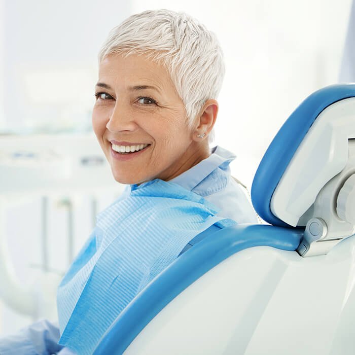 An old female patient happily sitting in a dental chair after sedation procedure