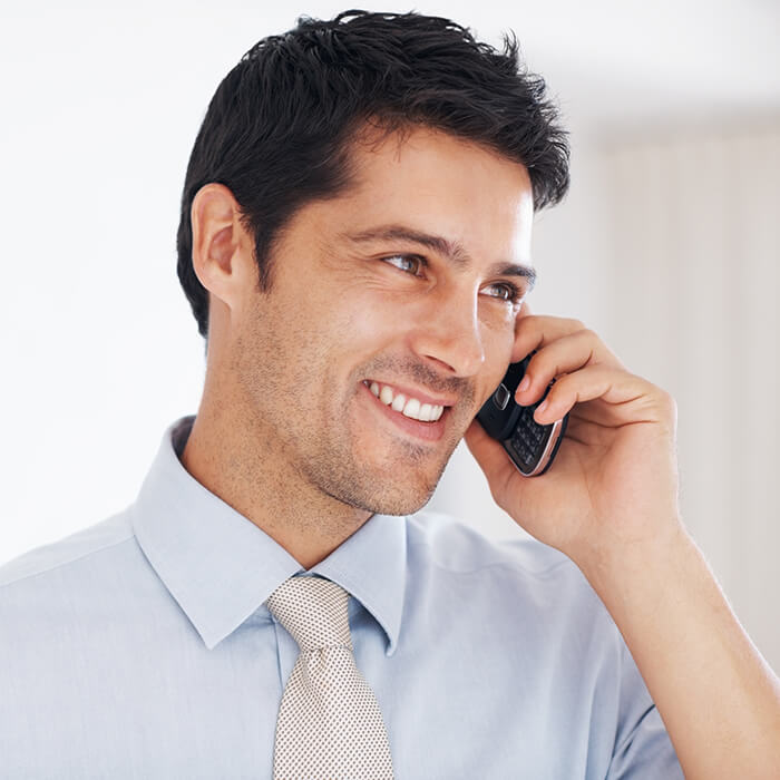 A man on a phone call with white smile
