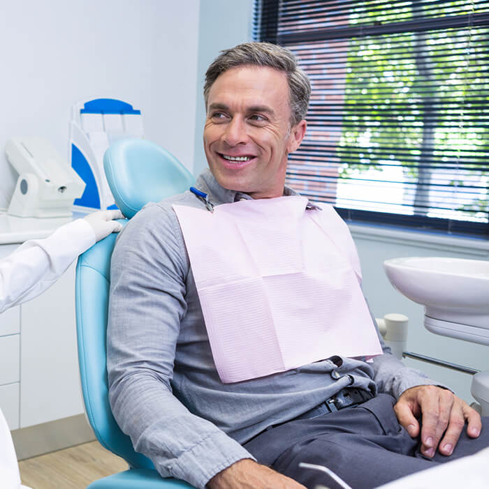 A man sitting in a dental chair smiling