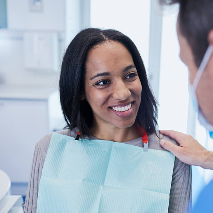 A female patient smiling and conversing with a team member