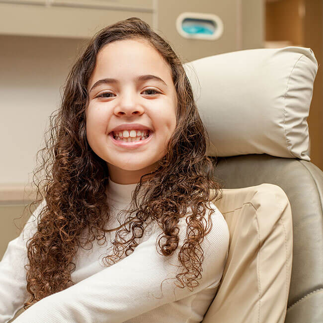 A young patient sitting in a dental chair and showing her white smile.