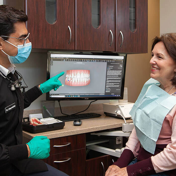Dr. Daniel pointing to the screen and explaining a dental procedure to a female patient smiling towards the dental doctor