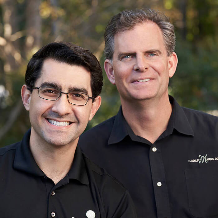 Dr. Charles and Dr. Daniel standing and smiling together both wearing a black polo