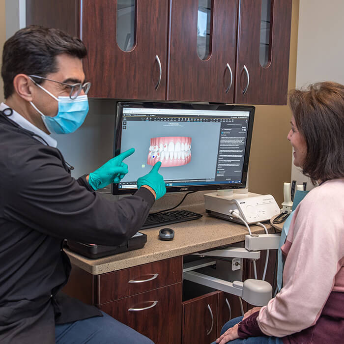 Dr. Daniel pointing to the screen and explaining a dental procedure to a female patient facing the screen