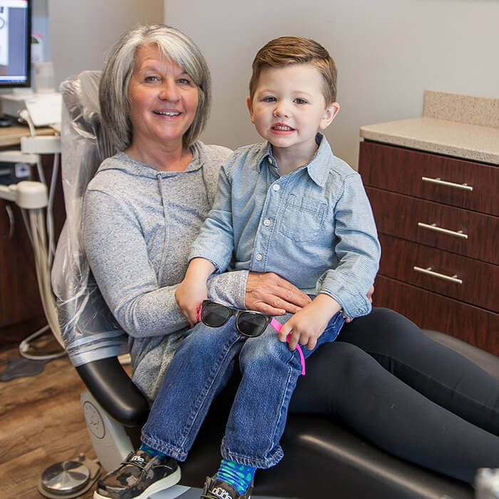 An old female patient sitting in a dental chair wearing a sweater and a little boy wearing a denim polo sitting on her lap
