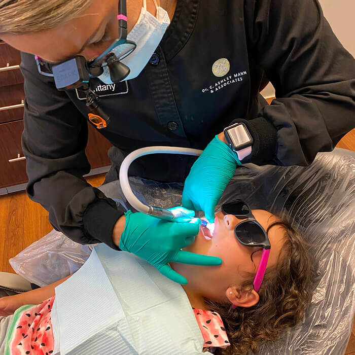 A team member doing a dental procedure to a female child patient while wearing a sunglass and lying in a dental chair