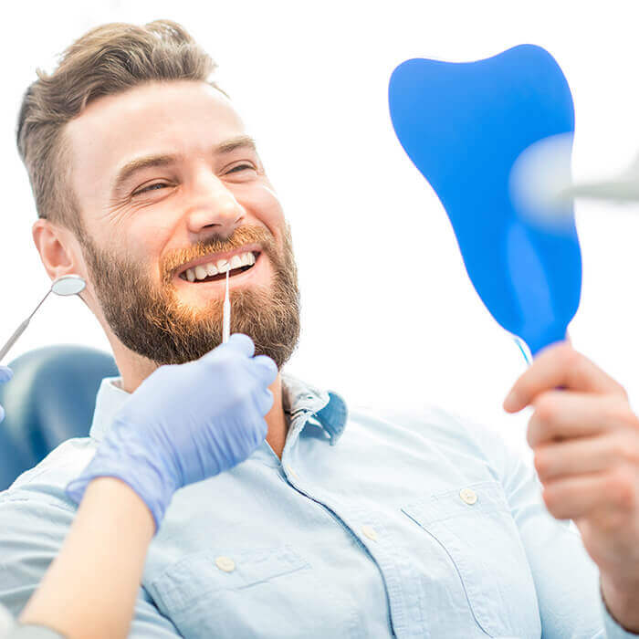 A male patient sitting in a dental chair holding a blue mirror and looking at his teeth