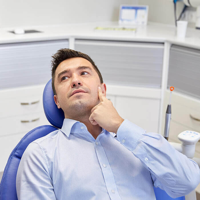 A male patient wearing a blue polo lying in a dental chair pointing at his cheek while looking towards a team member on his side