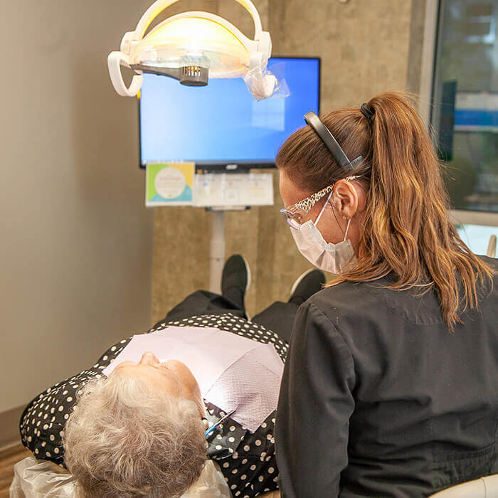 An old female patient lying in a dental chair during a dental procedure and a team member looking towards the patient