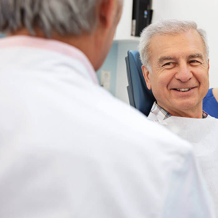 An old male patient sitting in a dental chair half-smiling towards the dental doctor