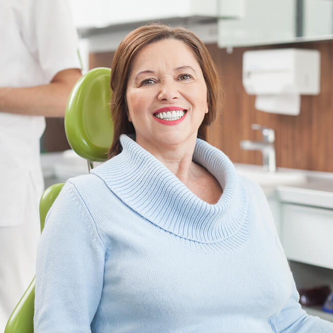 An old woman with white teeth wearing a blue sweaters sitting in a green dental chair