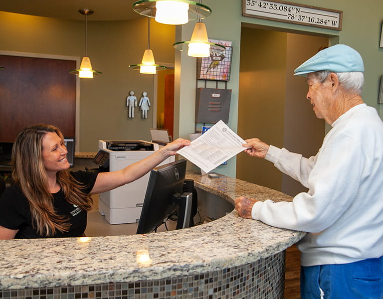 A team member in the reception area handling a form to an old man