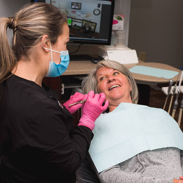 An old female patient lying in a dental chair wearing a dental bib and smiling towards a team member while talking to her